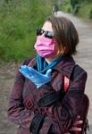 Frau mit Mund-Nasenschutz und Handschuhen